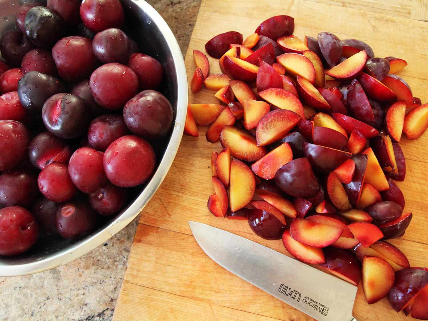 Sliced plum fruit on a wooden board next to a chef's knife, with a large metal bowl of whole plums nearby