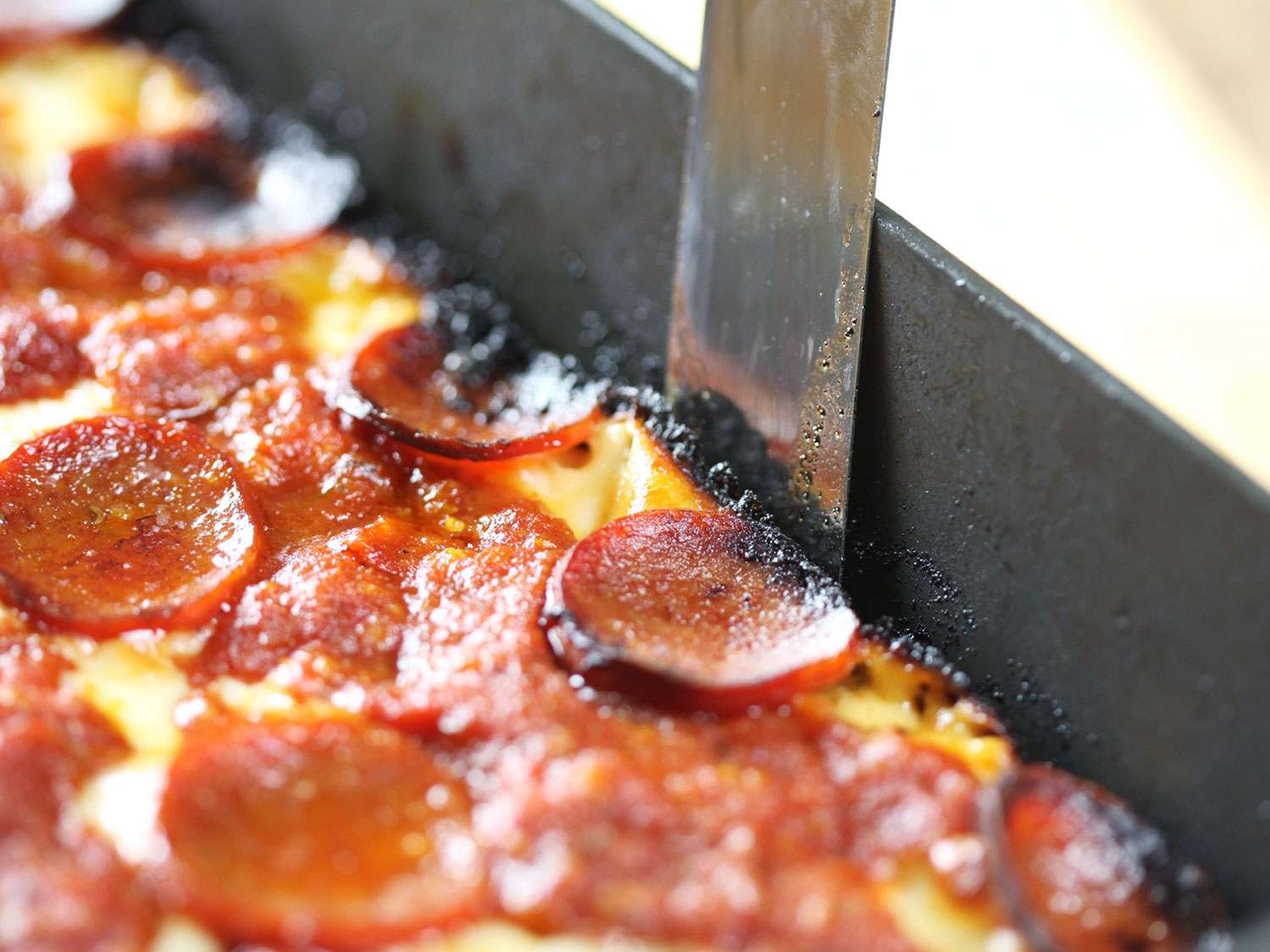 A flexible spatula sliding edges of Detroit-style pizza away from pan edge