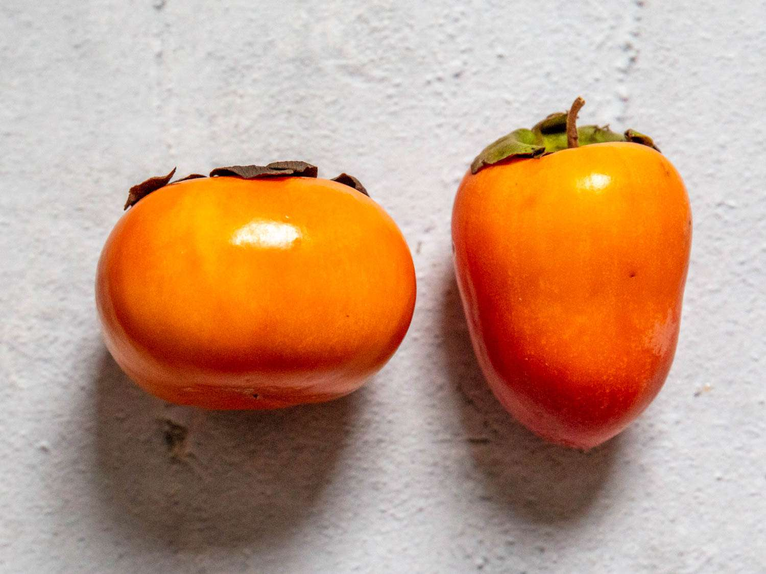 On the left: a fuyu persimmon. On the right, a tsurunoko persimmon.