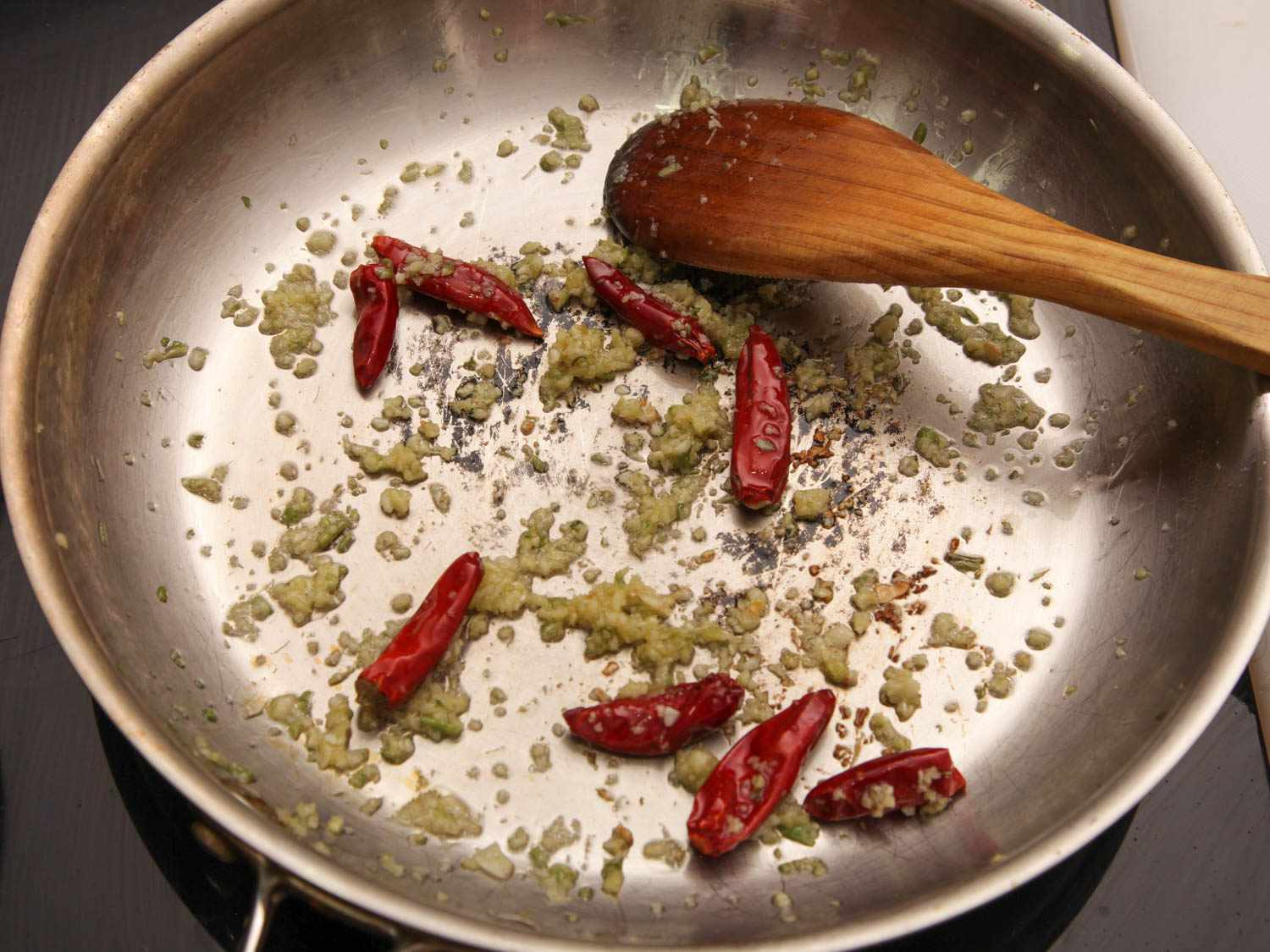Sauteing garlic and chiles in a stainless steel skillet for General Tso's chicken.