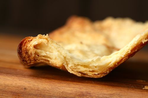 Close-up cutaway image of baked flaky pie crust showing layers.