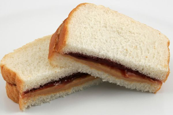 Peanut butter and jelly sandwich on white sliced bread, cut in half with the cut sides facing the camera.