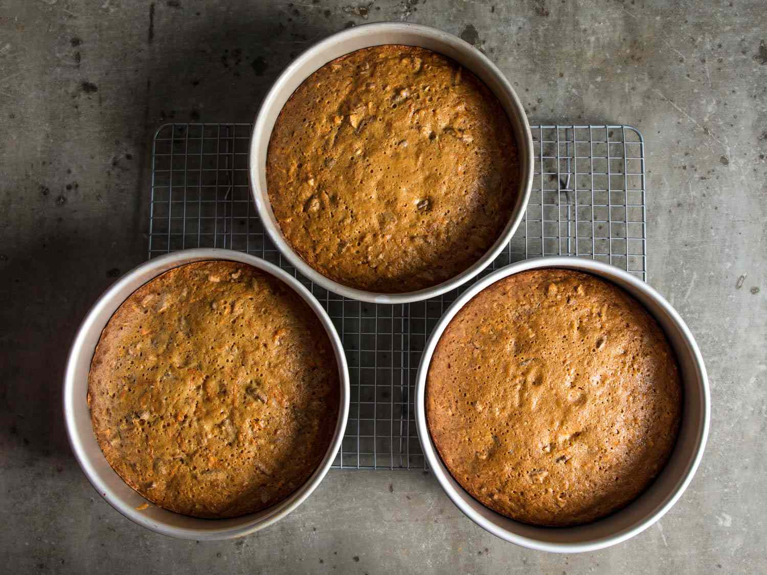 Overhead shot of three carrot cake layers cooling in their pans, on a wire rack