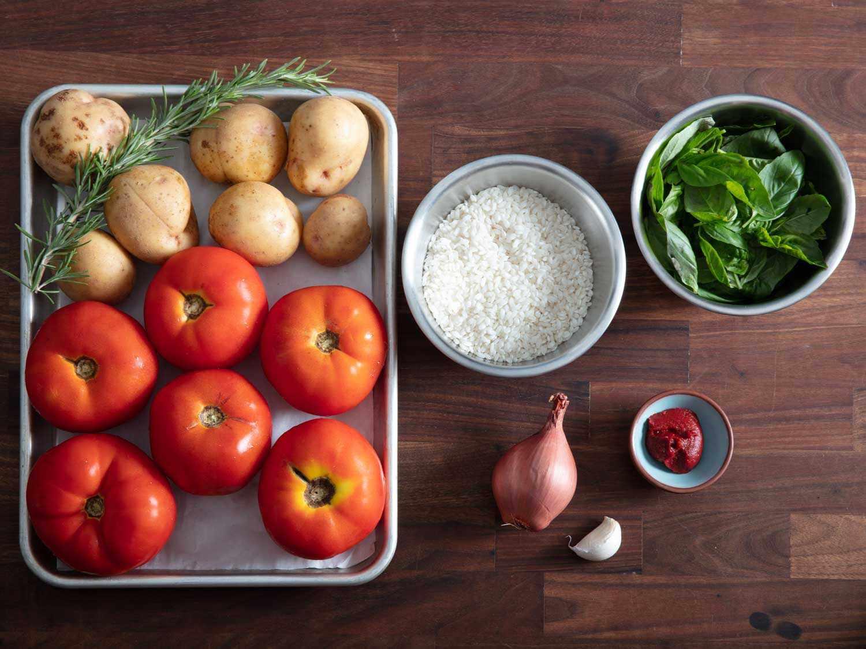 Overhead of ingredients for rice-stuffed tomatoes: potatoes, fresh rosemary, tomatoes, arborio rice, shallot, garlic, tomato paste, and fresh basil.