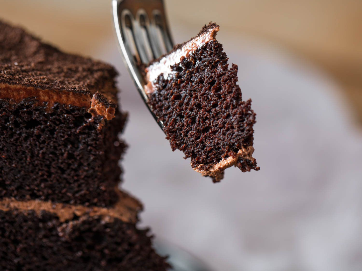 A fork pulling out a bite of chocolate Devil's food cake.
