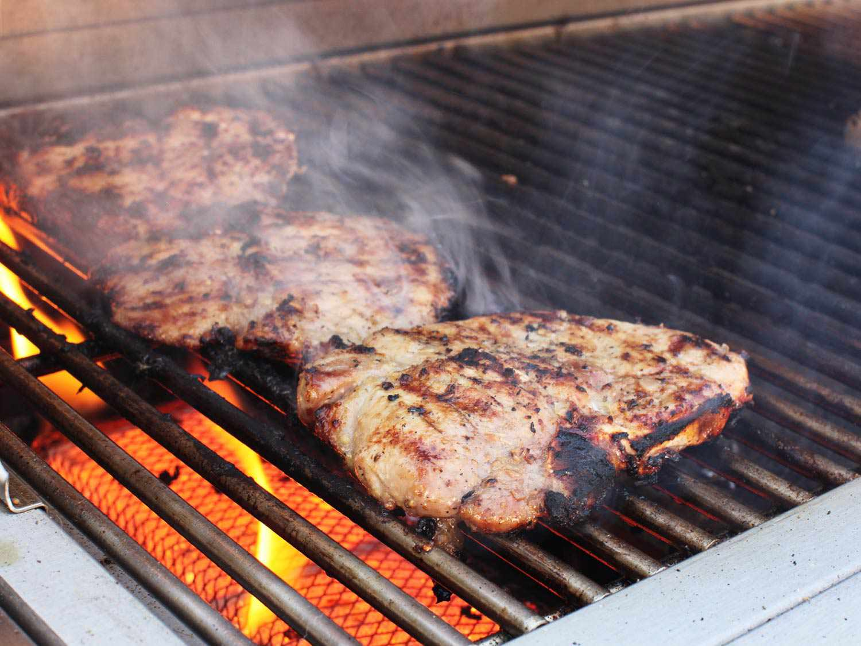Grilling Vietnamese lemongrass pork chops over high heat on gas grill.