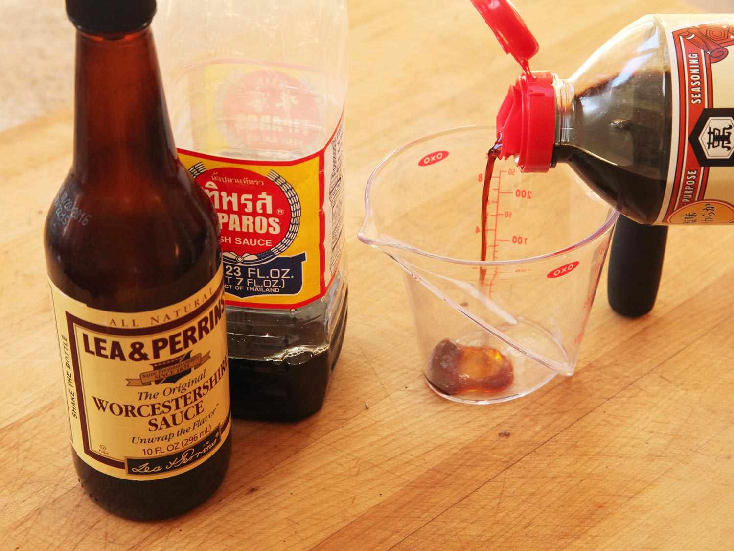 Bottles of Worcestershire sauce and fish sauce next to a measuring cup into which soy sauce is being poured.