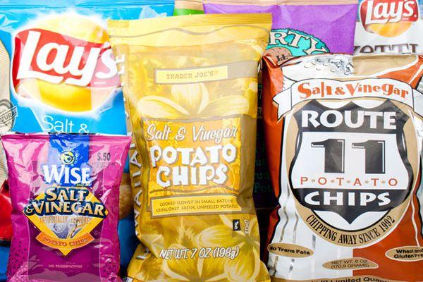 An assortment of bags of salt and vinegar potato chips.