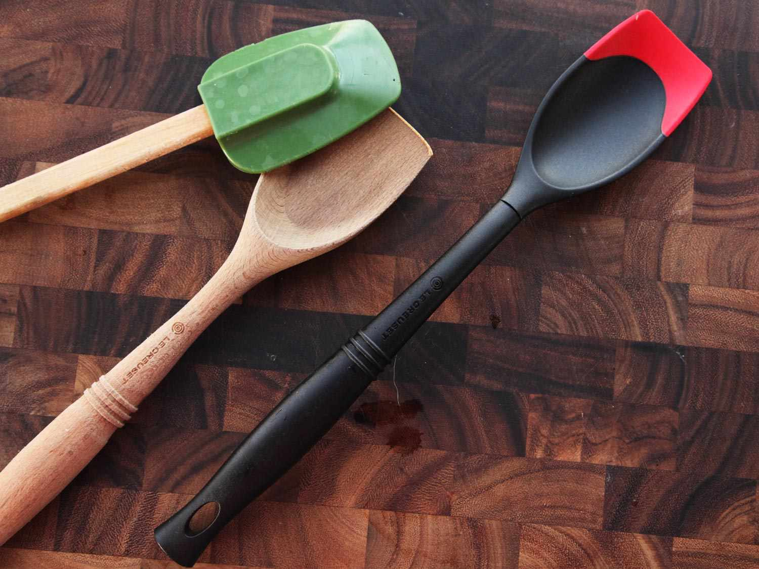 Three kinds of utensils: a spatula with a silicone head and wooden handle, a wooden scraping spoon, and a nylon scraping spoon