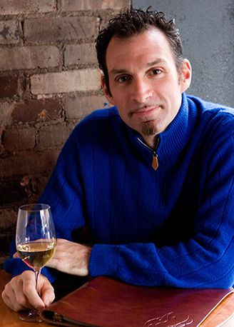 Sommelier in blue sweater, holding glass of white wine