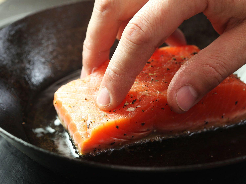 Pressing skin-on salmon fillet into a skillet of hot oil skin-side down.