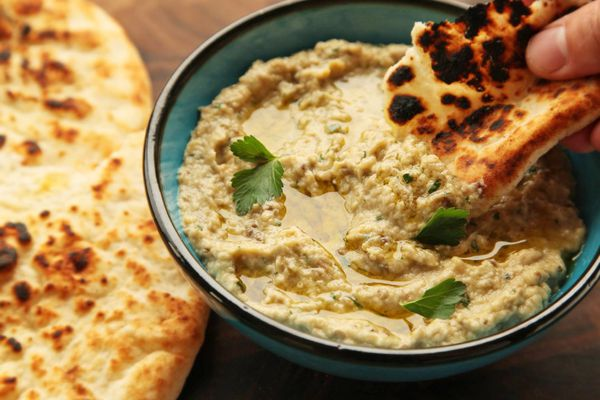 Dipping pita bread into baba ganoush in a small bowl, drizzled with olive oil.
