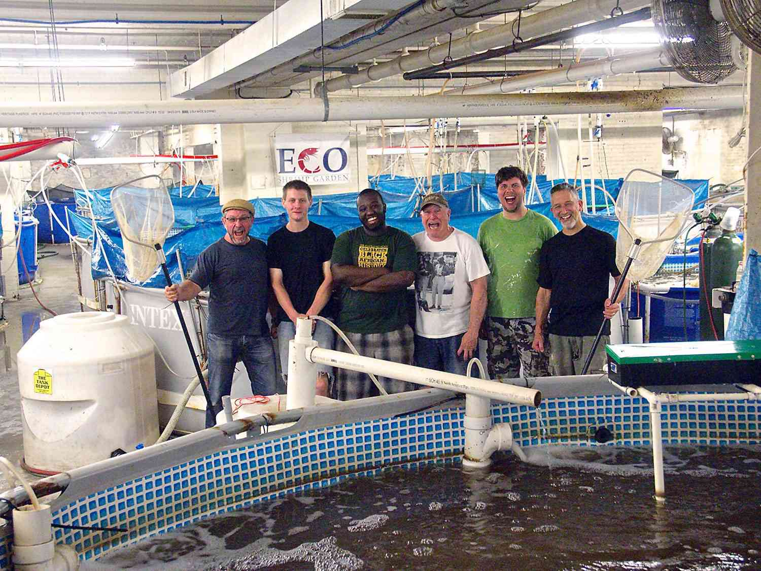 An early shrimp aquaculture setup used by Eco Shrimp Garden, with the company's staff (including Jean Claude Frajmund) standing nearby with nets