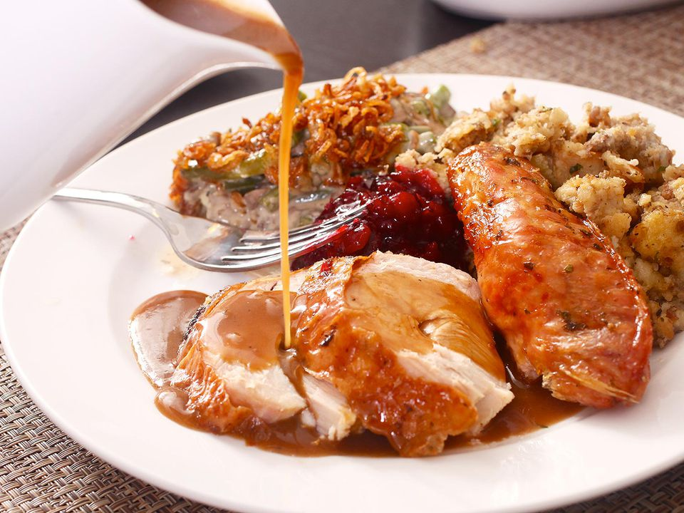 Gravy pouring over roast turkey plated with sides