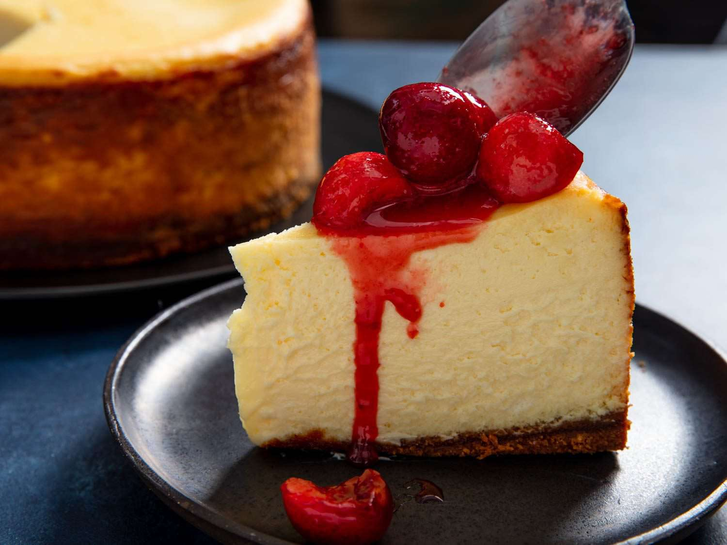 a slice of cheesecake topped with cherries