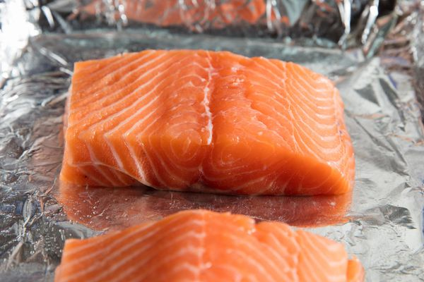 Two salmon fillets on a baking sheet that's lined with aluminum foil.