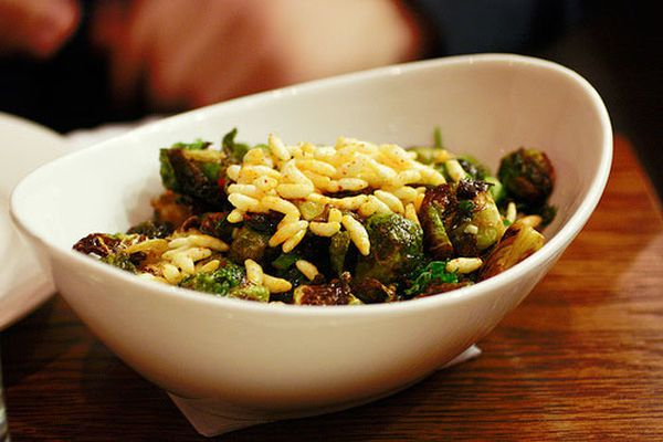 A white oval bowl of Momofuku Brussels sprouts topped with puffed rice.