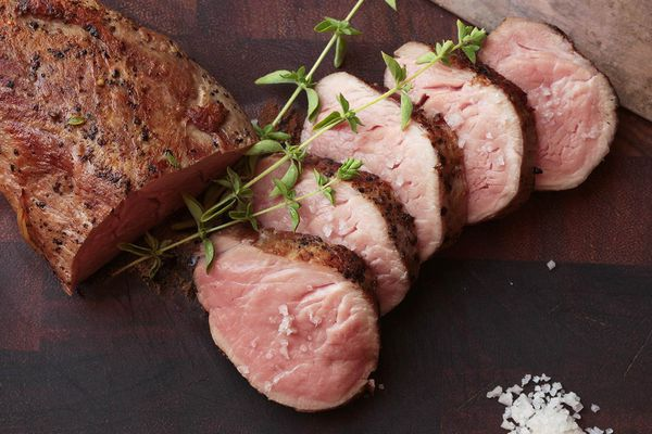Sliced sous vide pork tenderloin cooked medium rare and seared to form browned exterior.