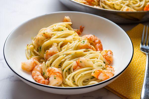 A bowl of shrimp scampi with pasta.