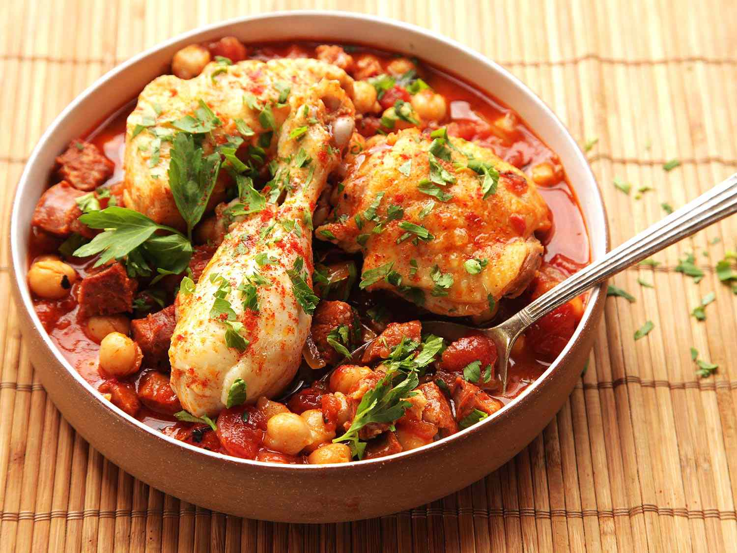 A serving bowl of 30-Minute Pressure Cooker Chicken With Chickpeas, Tomatoes, and Chorizo.