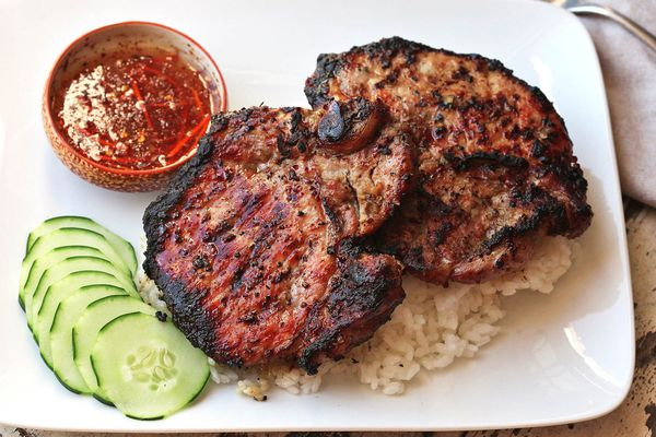 Grilled Vietnamese-style lemongrass pork chops on bed of rice with sliced cucumber and nuoc cham on the side.