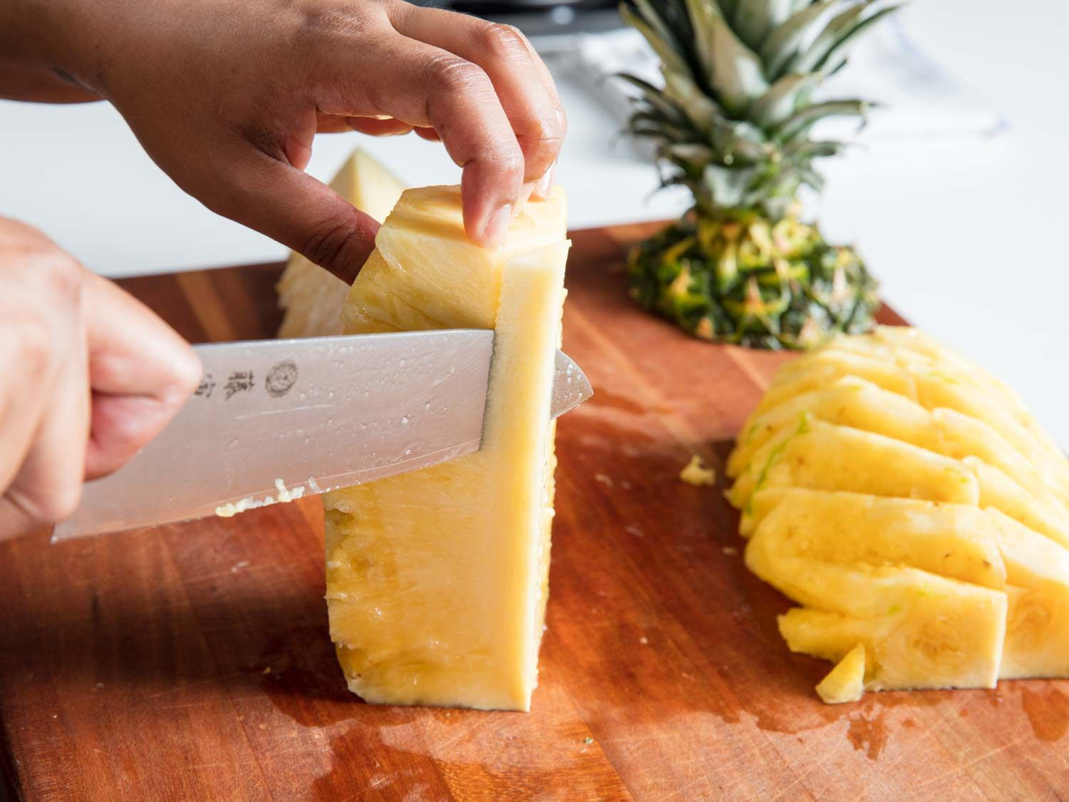 A knife trimming out the core of a pineapple.