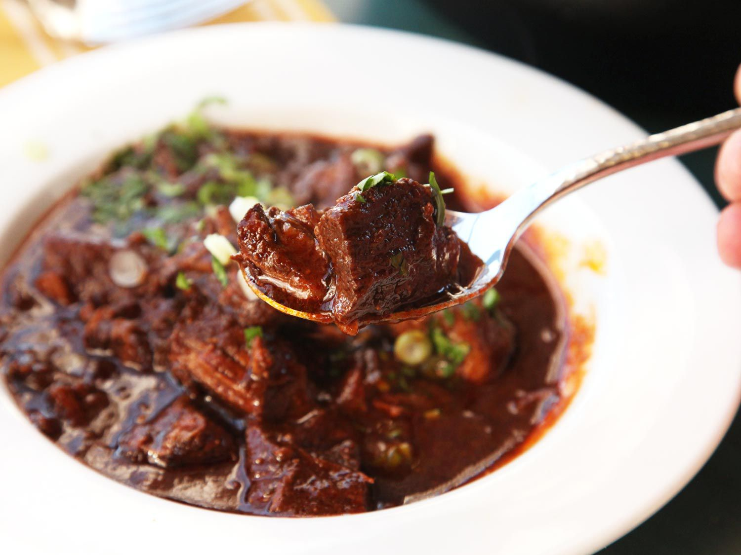 A bowl of Real Texas Chili con Carne, with a spoon of chili being held above the bowl.