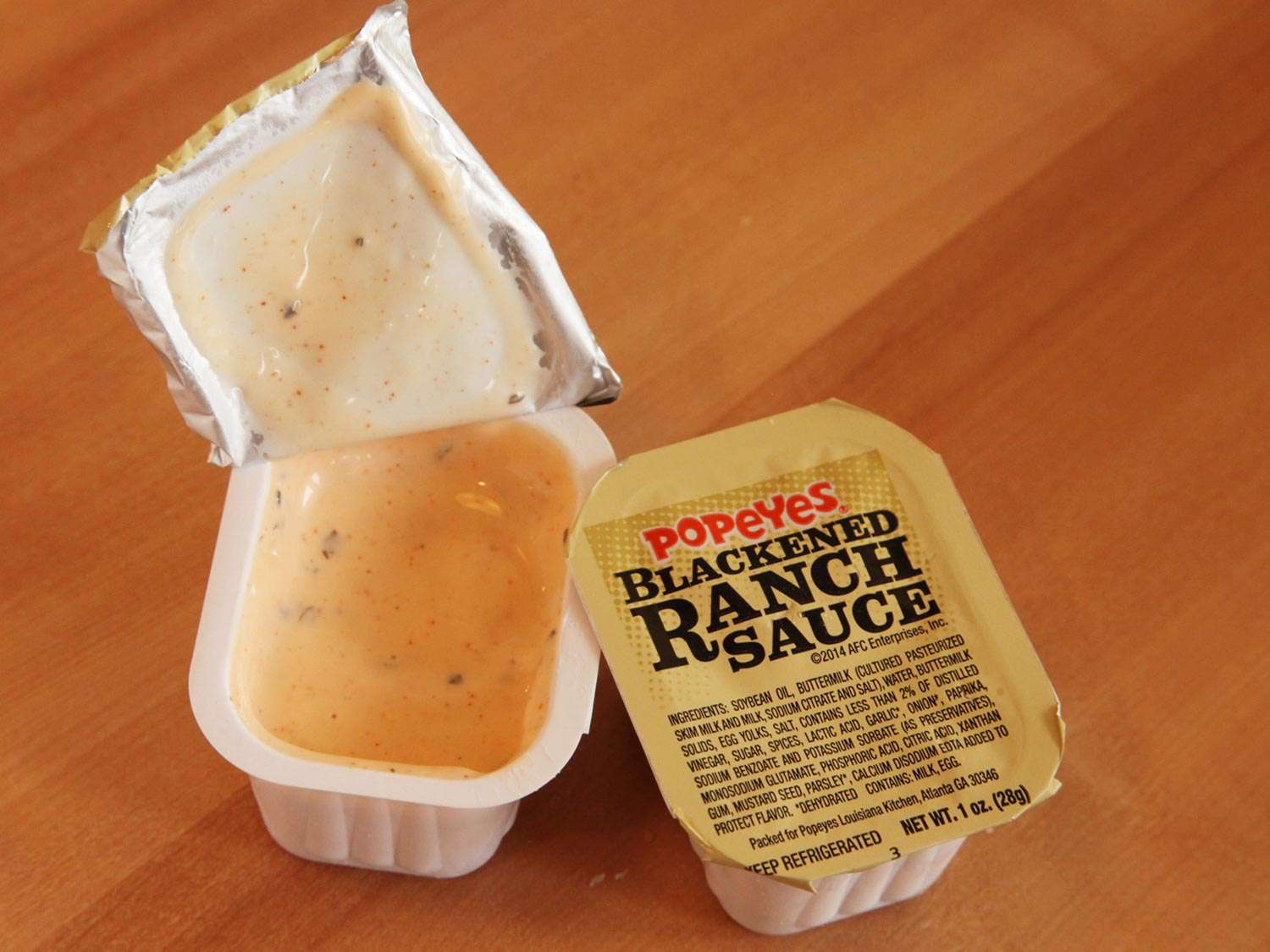 Two containers of blackened Ranch sauce from Popeye's
