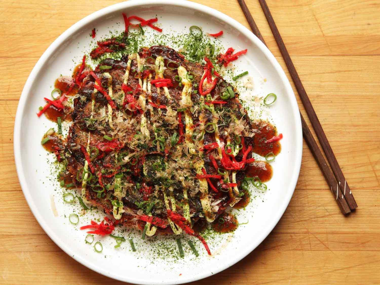 An okonomiyaki, a Japanese cabbage pancake, on a white plate with chopsticks near it.