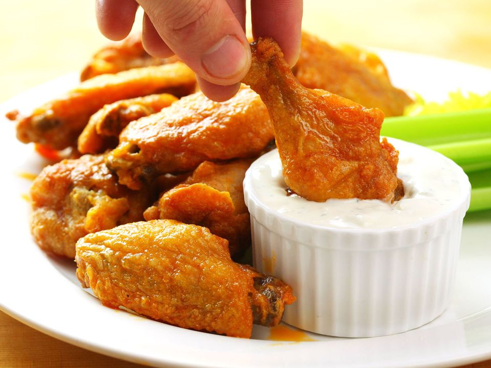 Dipping crispy baked buffalo wings into blue cheese dressing
