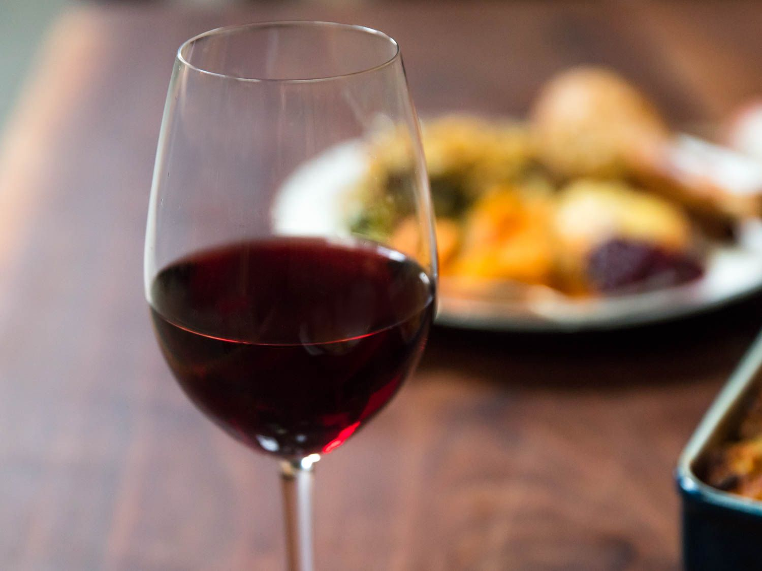 A glass of red wine sits on a table with a plate of food in the background