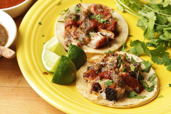A yellow plate with two small tacos de castacan con queso. There are also lime wedges and cilantro sprigs on the plate.