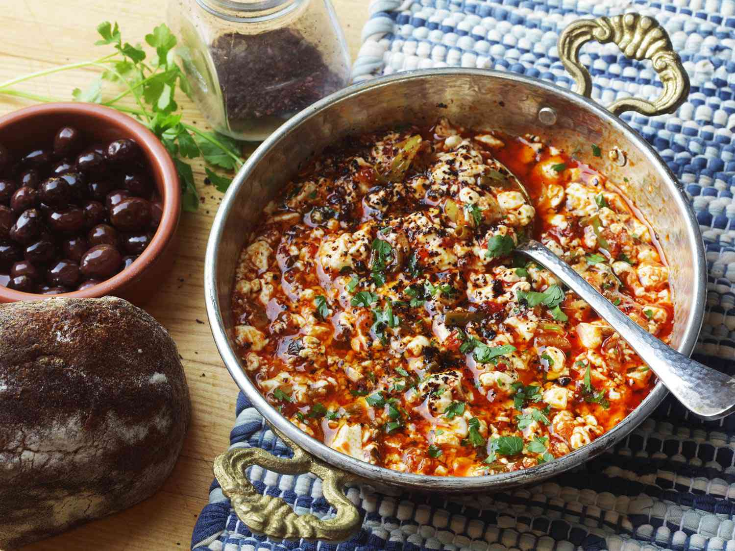 Turkish style vegan menemen in a Turkish style pan. There is a small dish of black olives next to it. .