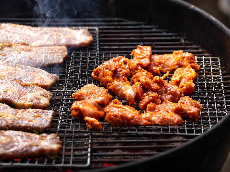 Chunks of pork shoulder for dwaeji bulgogi grilling on a mesh wire rack next to beef kalbi.