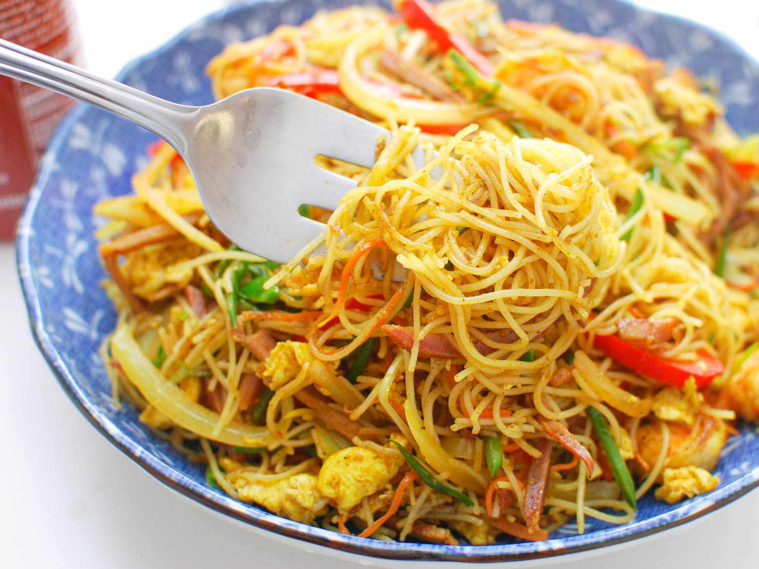 A fork twirling Singapore rice noodles from a bowl.