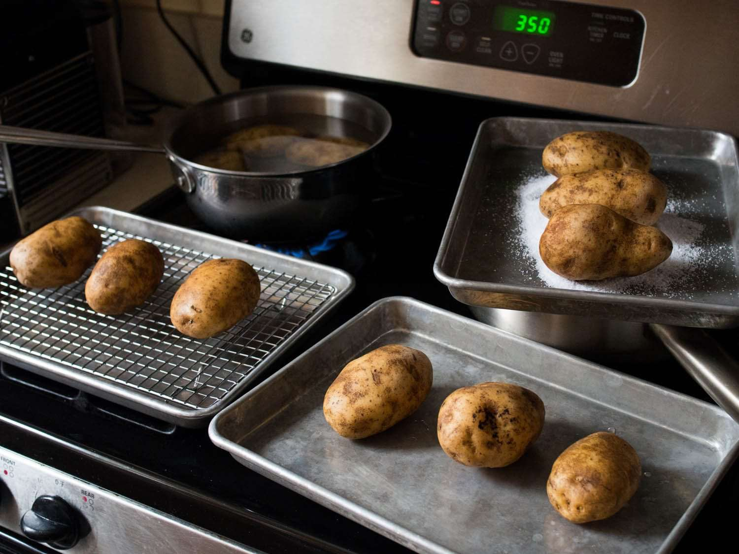 Three pans and one pot full of potatoes on a stovetop.