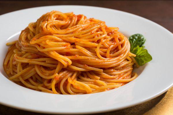 A shallow white bowl of spaghetti in fresh tomato sauce.