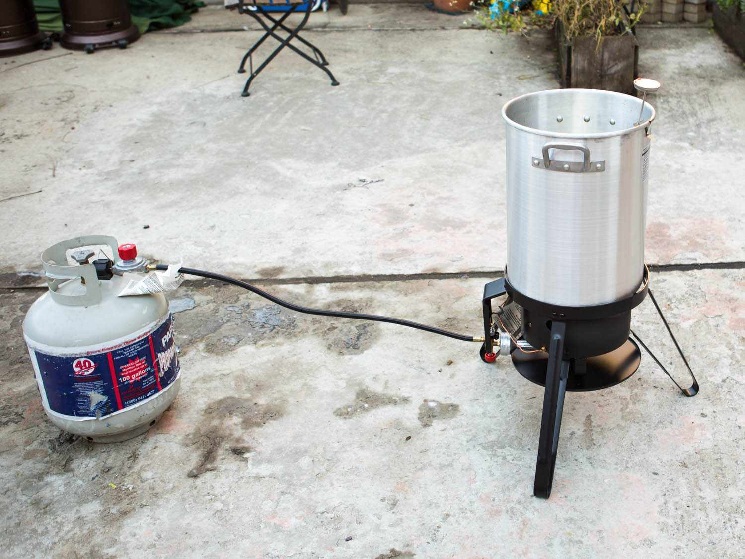 Demonstration of safe distance between propane gas tank and turkey fryer set up