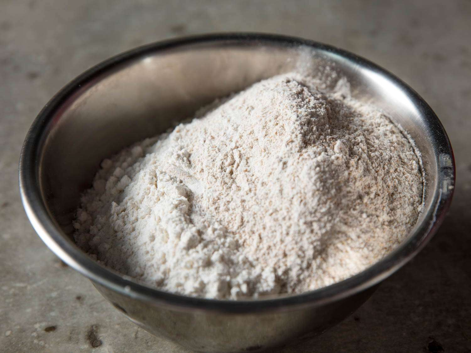 Whole wheat and all-purpose flours in a metal mixing bowl