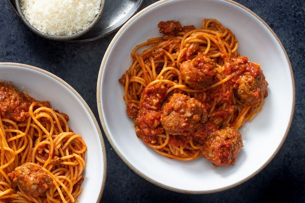 Two bowls of homemade spaghetti and meatballs with a dish of grated parmesan cheese next to them.