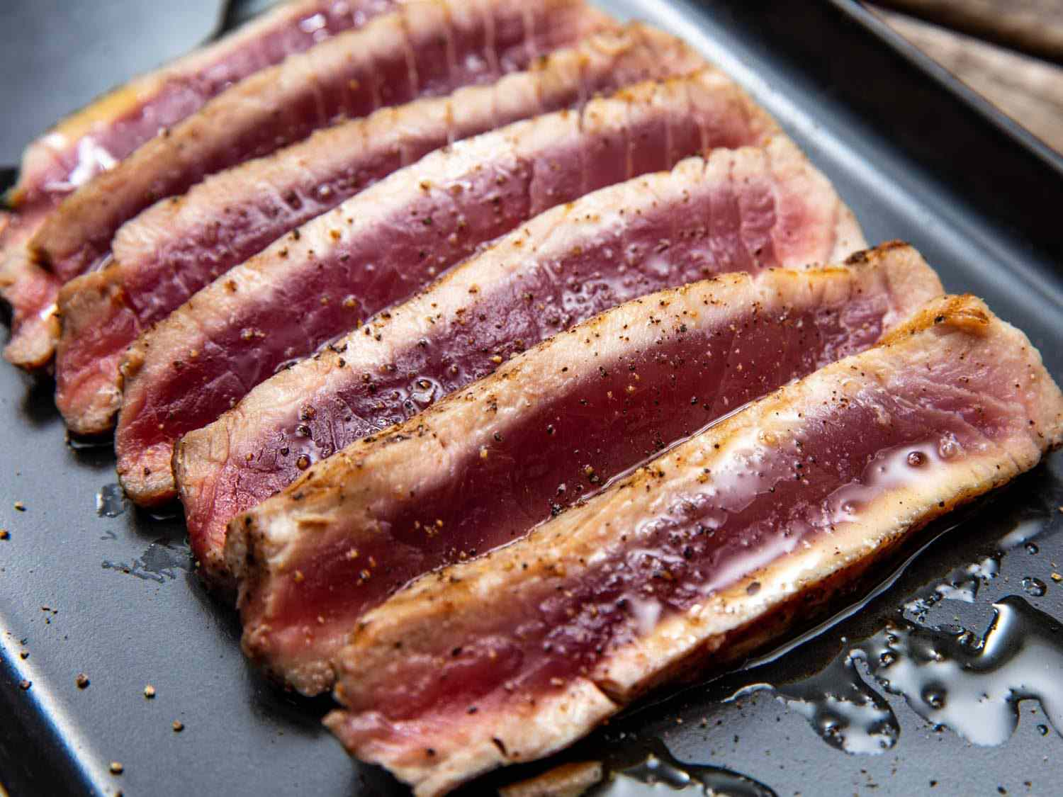 Slices of grilled tuna, cooked just around the edges and totally rare (raw, even) in the center, drizzled with olive oil and seasoned with salt and freshly ground black pepper