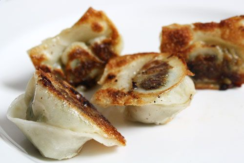 Seared wontons on a white plate.