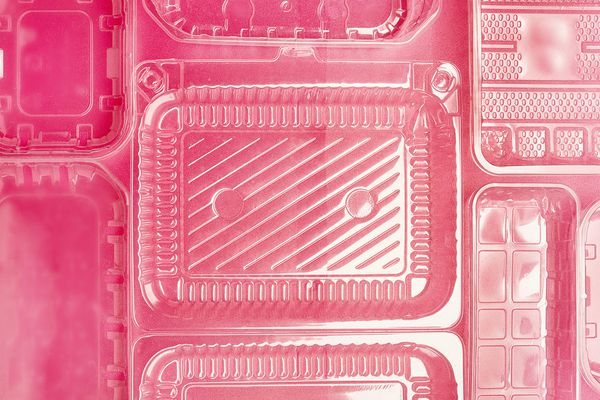 plastic clamshell containers on a pink background