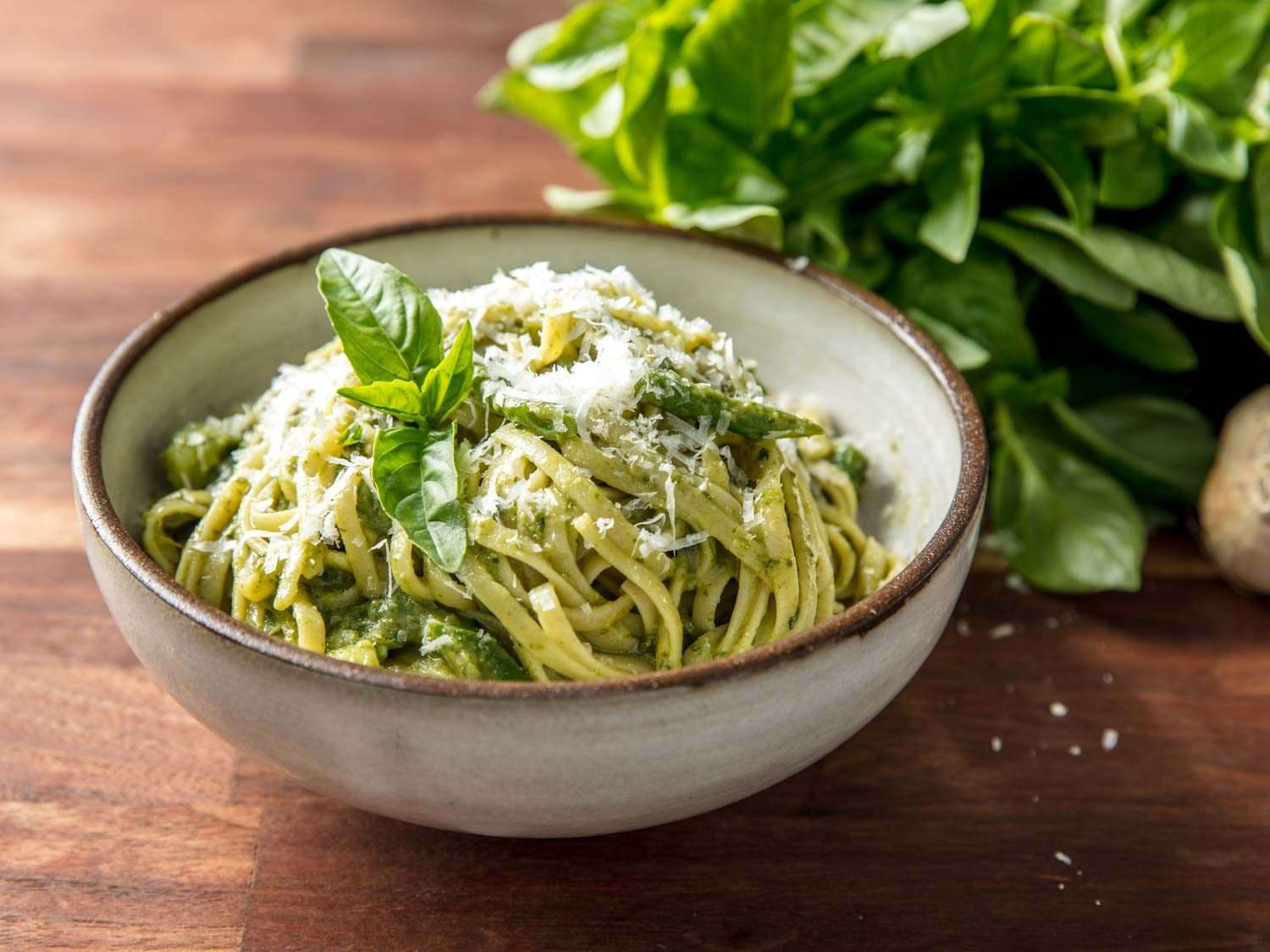 Pesto on linguine in a stone bowl, topped with cheese and basil leaves, with basil leaves in the background.