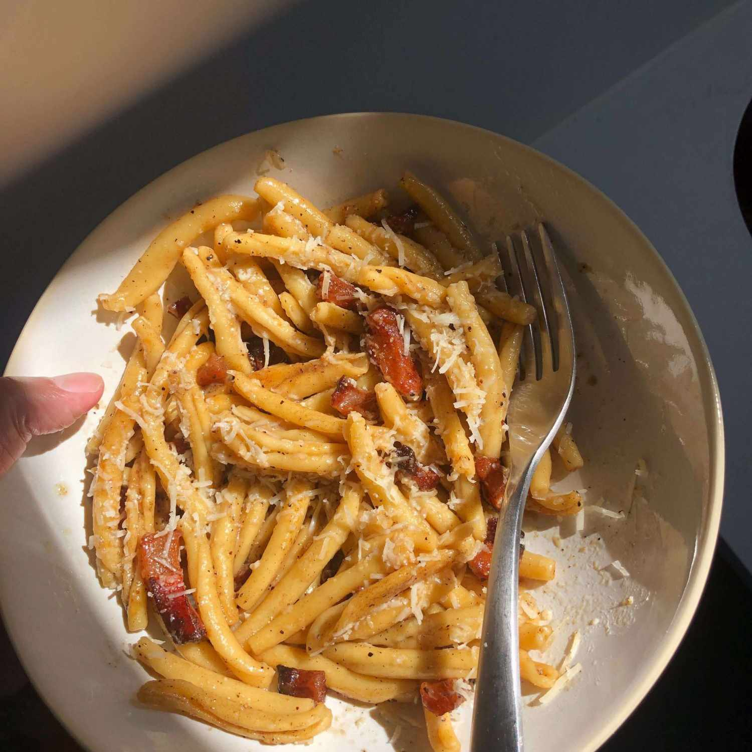 Joel's pasta alla gricia and weird thumb in a bowl