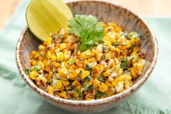 Easy esquites corn salad in a brown bowl with lime wedge.