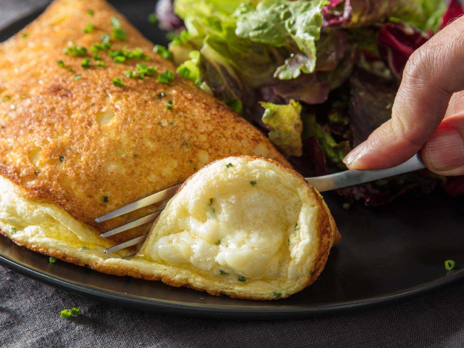 Using a fork to cut into a souffle omelette on a black plate with a salad on the side.