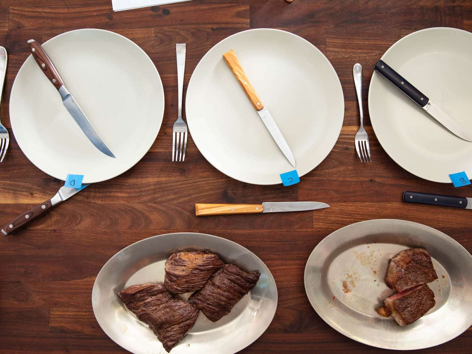 Overhead shot of the set-up for the steak knife equipment test, with different knives laid out with different cuts of cooked steak.