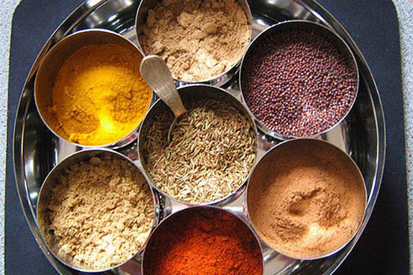 A collection of seven dry spices in a masala dabba, a large tin with smaller tins inside.