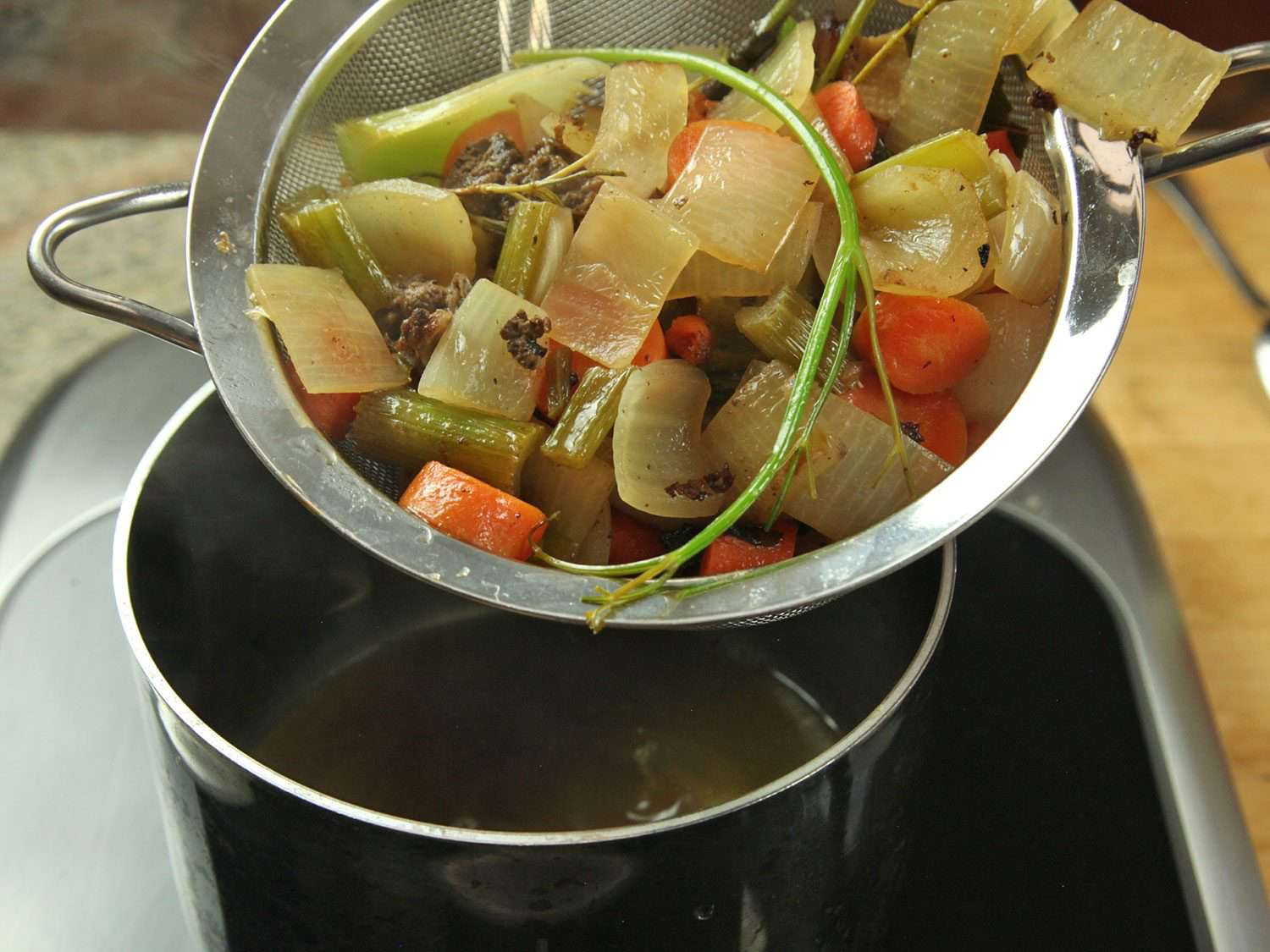 Straining vegetables and chicken back pieces out of a simmered jus mixture.